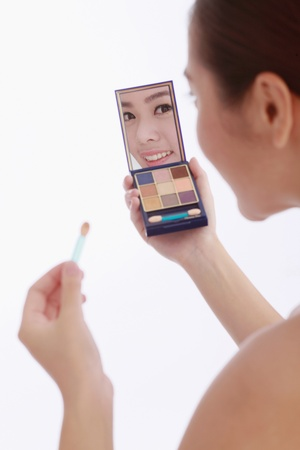 self conceit: Woman holding a compact mirror and applying eyeshadow Stock Photo