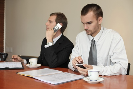 Businessman talking on the phone while his colleague is text messaging on the phone photo
