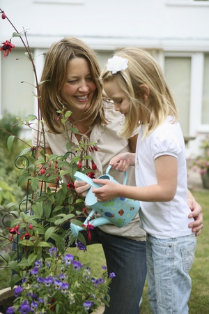 Woman and girl watering plants photo