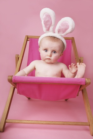 Baby boy with bunny ears relaxing on lounge chair Stock Photo - 13540162