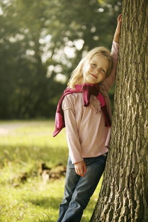 Girl posing next to a tree photo