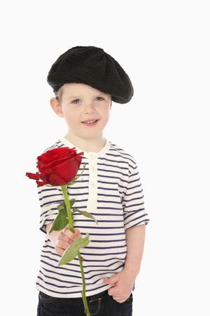 Boy in beret holding rose