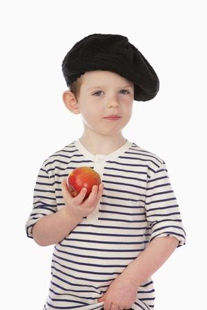 Boy in beret holding apple