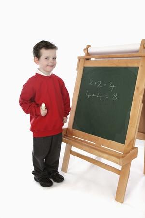 Boy solving equation on blackboard