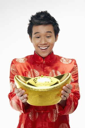 malaysia culture: Man holding a gold ingot