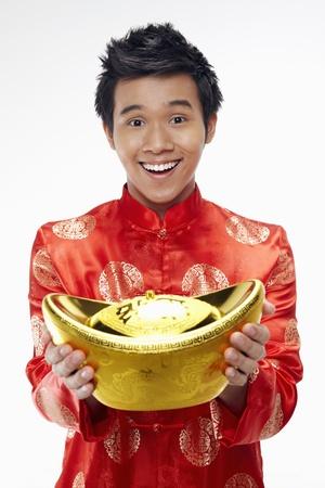 Man holding a gold ingot Stock Photo - 17130026