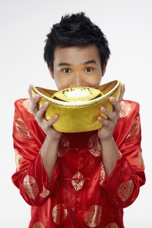 Man posing for the camera while holding a gold ingot Stock Photo - 17128871