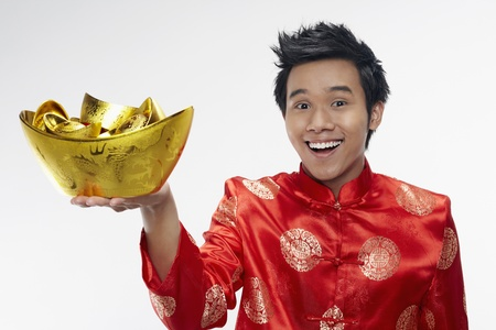 Man holding out gold ingots Stock Photo - 17128641