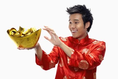 Man holding out gold ingots Stock Photo - 17130008