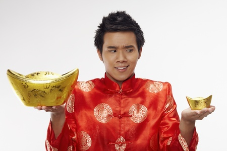 Man holding a big and small gold ingot with outstretched arms  Stock Photo - 17128878