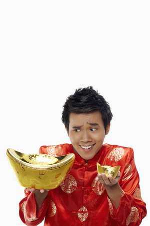 Man holding a big and small gold ingot with outstretched arms  Stock Photo - 17130009