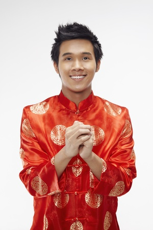Man in chinese traditional clothing showing greeting gesture Stock Photo - 17130024
