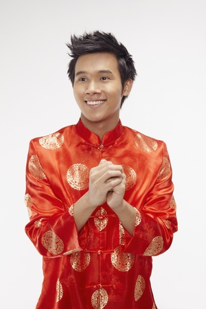 Man in chinese traditional clothing showing greeting gesture  Stock Photo - 17130022