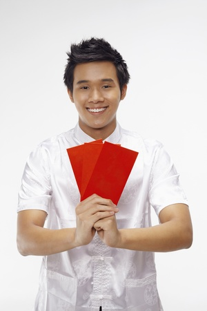 Man holding out red packets while showing greeting gesture  photo