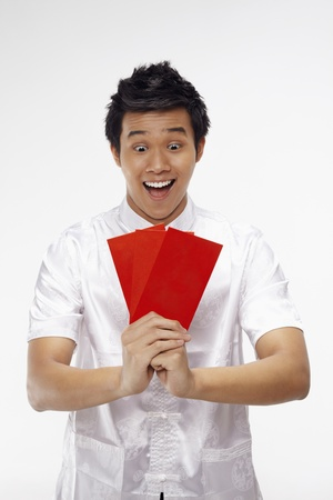 Man holding out red packets while showing greeting gesture