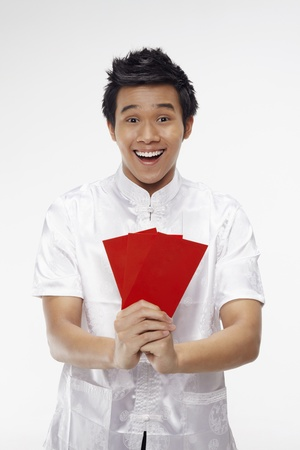 Man holding out red packets while showing greeting gesture  Stock Photo - 17130014
