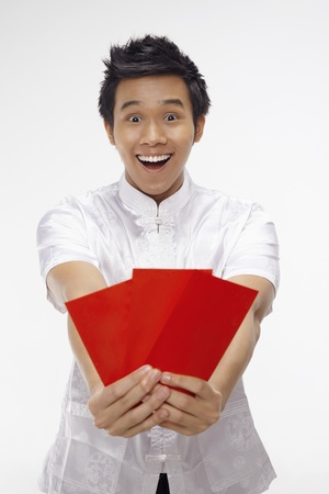 Man holding out red packets  photo