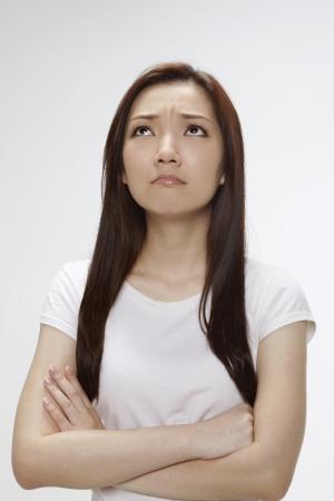 looking upwards: Sad woman frowning and looking upwards