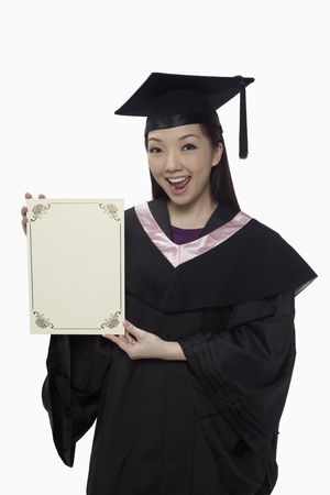 Woman in graduation robe holding blank certificate  photo