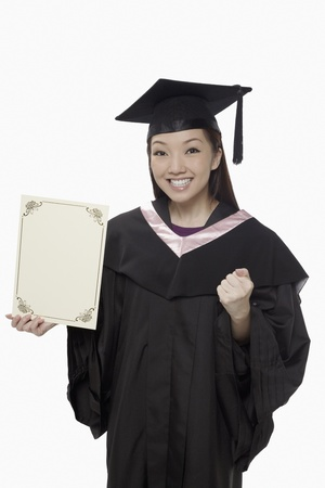 Woman in graduation robe holding blank certificate and cheering Stock Photo - 17255529