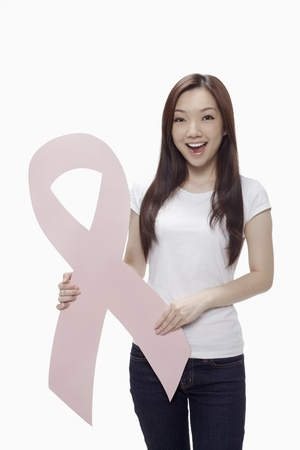 Woman smiling while holding a pink breast cancer ribbon  Stock Photo - 17255565