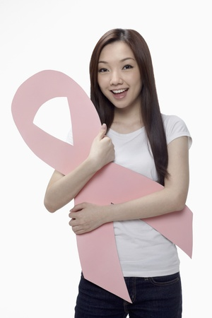 Woman smiling while holding a pink breast cancer ribbon