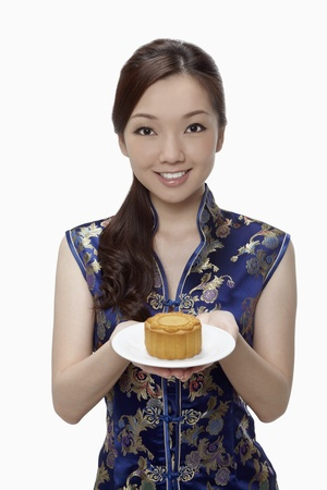 Woman in cheongsam offering mooncake on a plate Stock Photo - 17255530