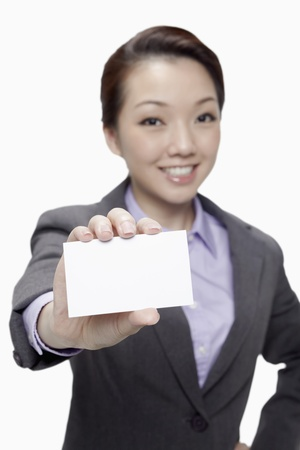 Businesswoman holding up her business card, focus on foreground  Stock Photo - 17255601