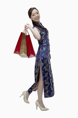 Woman in cheongsam holding shopping bags  Stock Photo - 17255594