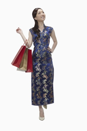 Woman in cheongsam holding shopping bags Stock Photo - 17255590