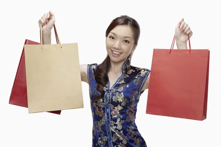 Woman in cheongsam holding up shopping bags  Stock Photo - 17255598