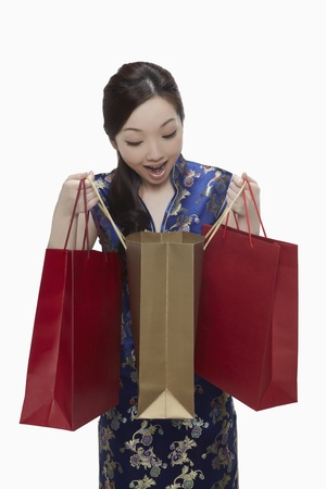 Woman in cheongsam looking into shopping bag  Stock Photo - 17255596