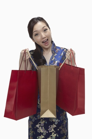 Woman in cheongsam with shopping bags looking excited  Stock Photo - 17255599