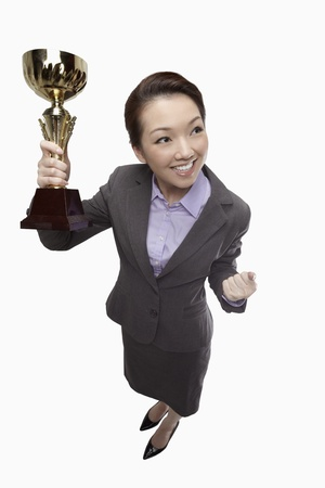 Businesswoman holding a trophy and cheering from success  photo