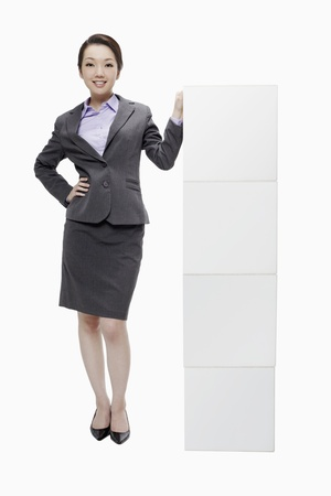Businesswoman standing beside stacked boxes  photo