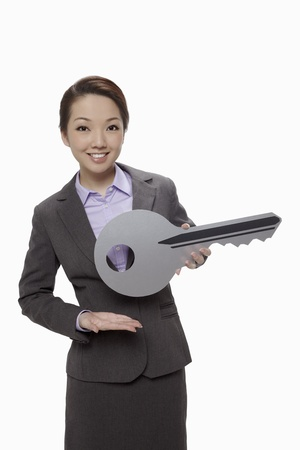 Businesswoman presenting a big key  photo