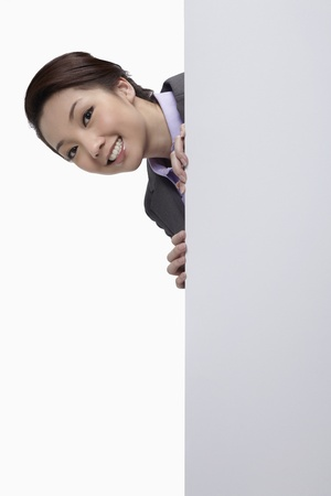 Businesswoman hiding behind blank placard, head popping out  photo