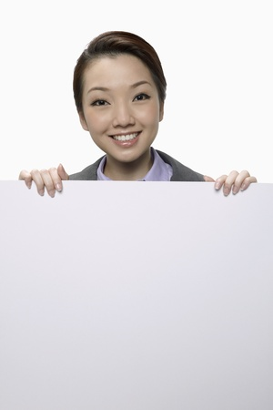 Smiling businesswoman standing behind blank placard  photo