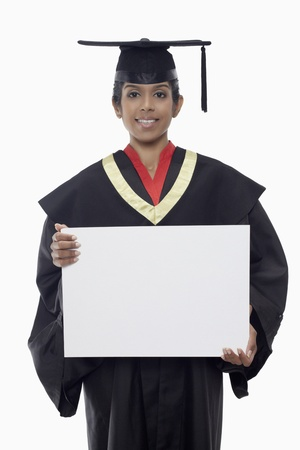 Woman in graduation robe holding a blank placard photo