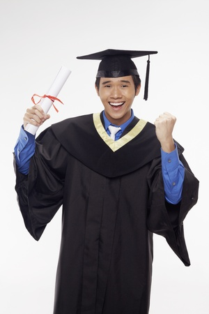Man in graduation robe holding his diploma scroll and cheering Stock Photo - 17340302