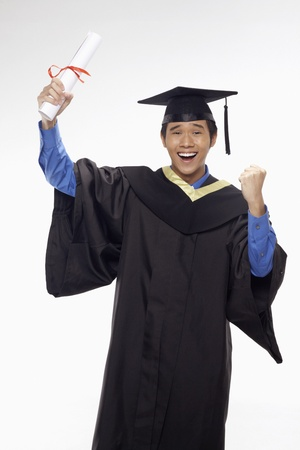 Man in graduation robe holding his diploma scroll and cheering photo