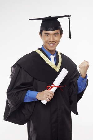 Man in graduation robe holding his diploma scroll and cheering Stock Photo - 17340260