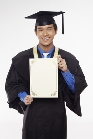 Man in graduation robe holding blank certificate Stock Photo - 17340265