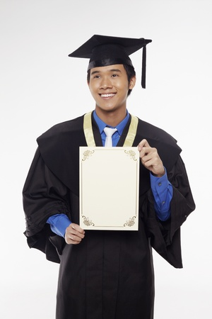 Man in graduation robe holding blank certificate Stock Photo - 17340293
