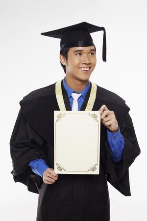 Man in graduation robe holding blank certificate Stock Photo - 17340261