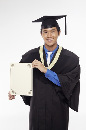 Man in graduation robe holding blank certificate Stock Photo - 17340280