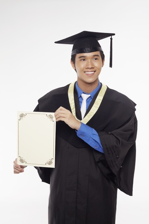 Man in graduation robe holding blank certificate photo