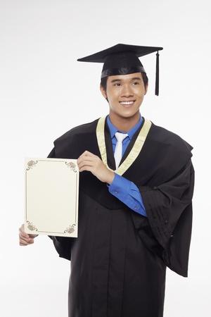 Man in graduation robe holding blank certificate Stock Photo - 17340281
