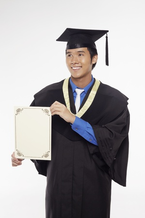 Man in graduation robe holding blank certificate Stock Photo - 17340274