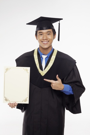 Man in graduation robe holding blank certificate Stock Photo - 17340311